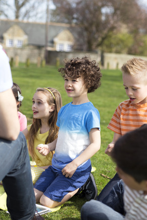non uniform: Small group of children sitting on the grass having a lesson outdoors. Only side of the teacher can be seen. The children look to be listening.