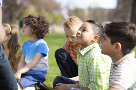 Small group of children sitting on the grass having a lesson outdoors. Only side of the teacher can be seen. The children look to be listening.