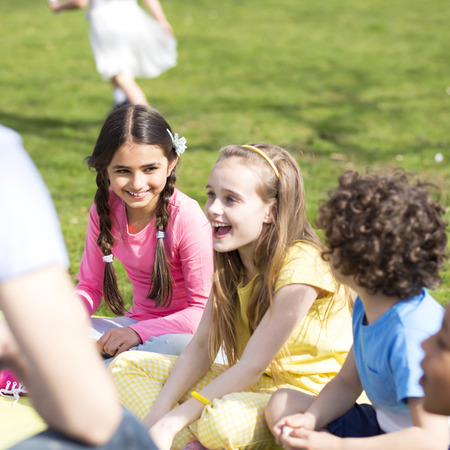 non uniform: Small group of children sitting on the grass having a lesson outdoors. Only side of the teacher can be seen. The children look to be listening and enjoying themself.