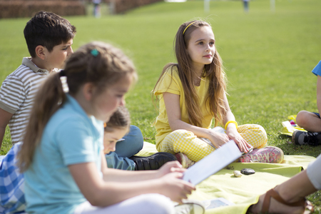 non uniform: Small group of children sitting on the grass having a lesson outdoors. The children look to be listening and enjoying themself. Stock Photo