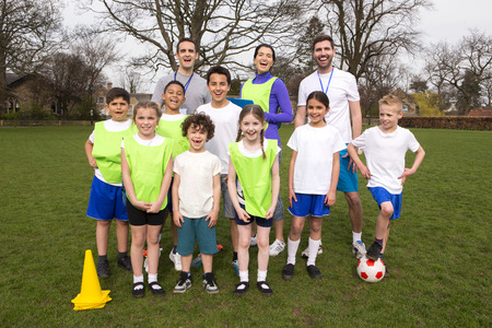 A group portrait of a kids soccer team, behind them are their coaches. They are all smiling and look happy. Stock Photo