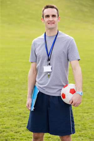 physical education: A male sports teacher stands outdoors in a field, he is holding a clipboard and football