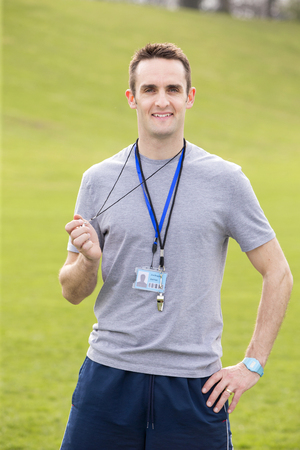 A male sports teacher stands outdoors on a field, he is holding a whistle.