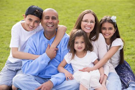 混合民族家族、ママとパパの肖像 4 に 10 の年齢の間の 3 人のかわいい子供があります。彼らは座って、カメラで幸せそうに笑っています。 写真素材 - 43374615