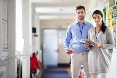 Twee leerkrachten staan in een school gang, ze zijn allebei gekleed smart casual en kijken ernstig
