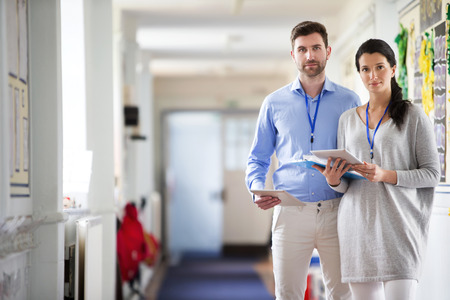 typically british: Two teachers standing in a school corridor, they are both dressed smart casual and look serious Stock Photo