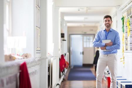 maestra: Un profesor de sexo masculino feliz vestida elegantemente y sonriendo en un pasillo de la escuela.
