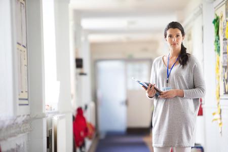 maestra enseñando: Un profesor feliz hembra vestida elegantemente y sonriendo en un pasillo de la escuela. Foto de archivo
