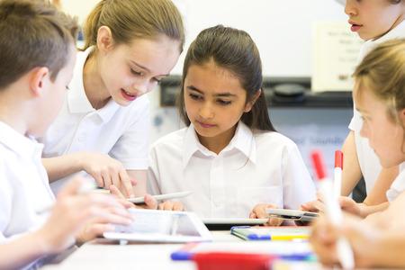 학교 어린이의 그룹이 디지털 정제 작업을 볼 수 있습니다, 그들은 모두 행복하게 일하고있다.
