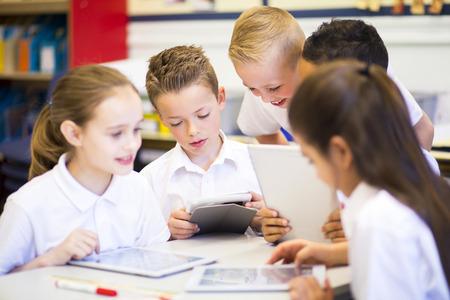 ni�as peque�as: Estudiantes felices en el aula utilizando una tableta digital, todos ellos est�n usando los uniformes.