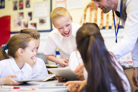 typically british: Happy students in classroom using a digital tablet, they are all wearing uniforms.