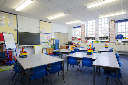 A horizontal image of an empty primary school classroom. The setting is typically British.
