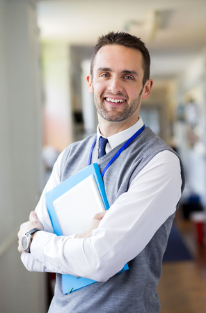 A happy male teacher dressed smartly and smiling in a school corridor. He is holding folders and a digital tablet.