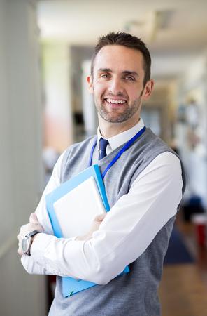 profesores: Un profesor de sexo masculino feliz vestida elegantemente y sonriendo en un pasillo de la escuela. Él es la celebración de carpetas y una tableta digital.