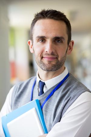 edificio escuela: Un profesor de sexo masculino feliz vestida elegantemente y sonriendo en un pasillo de la escuela. �l es la celebraci�n de carpetas y una tableta digital.