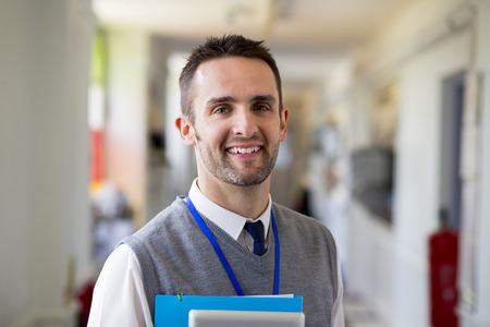 maestra enseñando: Un profesor de sexo masculino feliz vestida elegantemente y sonriendo en un pasillo de la escuela. Él es la celebración de carpetas y una tableta digital.
