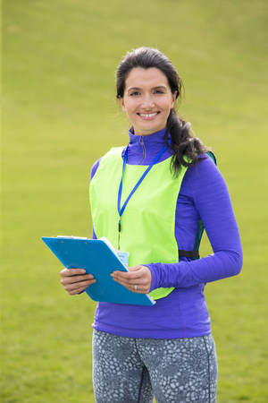 late 20s: A female sports teacher stands outdoors in a field, she is holding a clipboard and smiling.