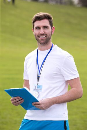 A male sports teacher stands outdoors on a field, he is holding a clipboard.
