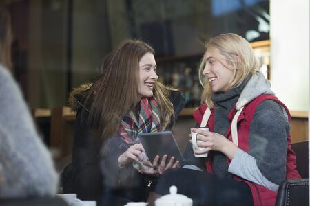 coffees: Two women are sitting in a cafe. They are talking and looking at a digital tablet with coffees in their hand. Stock Photo