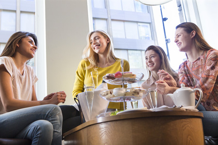 Four young women sitting in a cafe together, talking over afternoon tea. 版權商用圖片