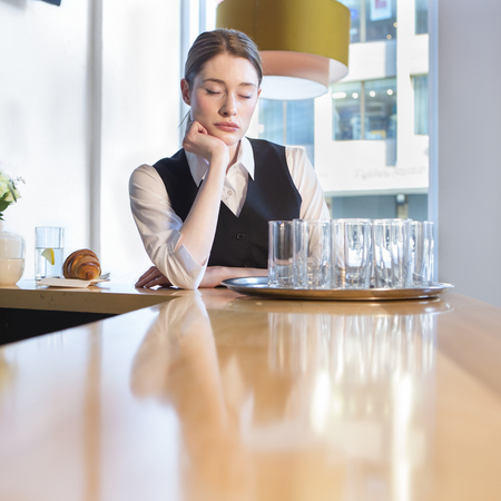 attractive female: Fed up waitress at work. She has her eyes closed and is resting her head on her hand at the bar, with a tray of dirty glasses in front of her. Stock Photo