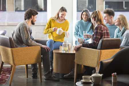chatting: Group of friends having afternoon tea together in a cafe. Stock Photo