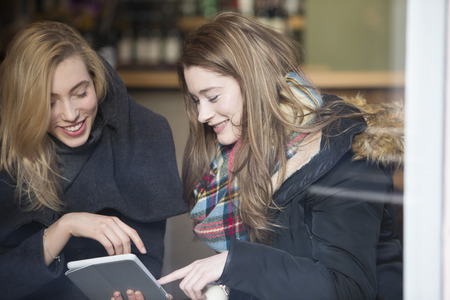 two women talking: Two women are sitting in a cafe. They are talking and looking at a digital tablet. Stock Photo