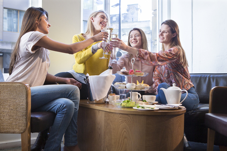 Four women toasting champagne over afternoon tea in a cafe. 版權商用圖片