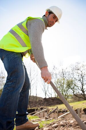 engineering tool: Male construction worker clearing the ground using gardening equipment