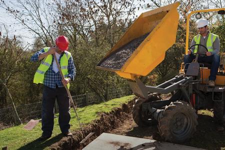 maquinaria pesada: Dos trabajadores de la construcción masculinos utilizando maquinaria pesada