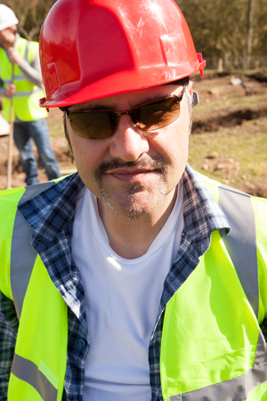 high visibility: Male construction worker smiling at camera with partner working in background