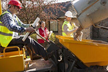 maquinaria pesada: Trabajadores de la construcción masculinos utilizando maquinaria pesada siendo observados por el organizador femenina Foto de archivo