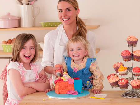 piping: Mother decorating cakes with her two daughters