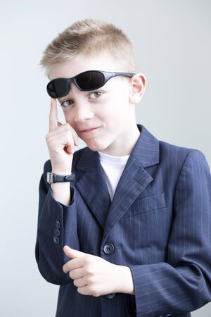 funny boy: Young boy dressed up and posing like a spy. He is wearing a suit with sunglasses on his head and a formal watch. He is miming a gun with his hands. Stock Photo