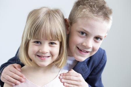 girl pose: Young boy and girl dressed up formally and posing for the camera together on a white background Stock Photo