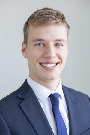 Close up portrait of a formally presented young man, smiling for the camera on a white background