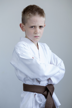 karate boy: Young boy in karate clothing, posing with a tough expression on his face and his arms folded.