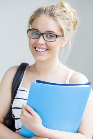 blonde yeux bleus: Attractive adolescente posant avec des dossiers sur un fond uni Banque d'images