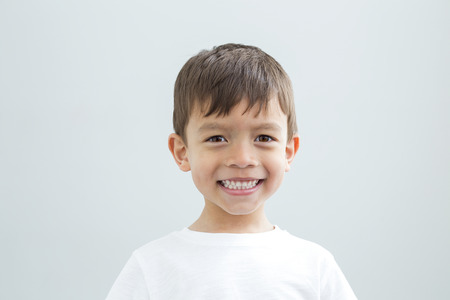 Landscape headshot of a young boy against a plain background