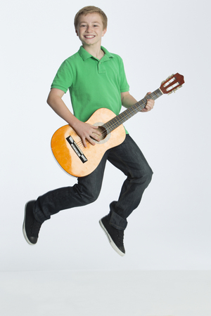 playing music: Young boy jumping whilst playing guitar. He is smiling at the camera and is against a plain background.