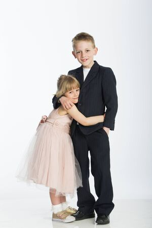 formally: Formally dressed brother and sister. They are hugging and smiling for the camera against a white background