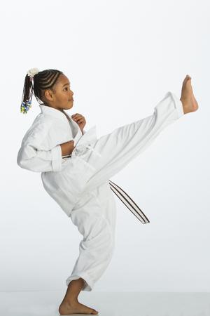 patada: niña de raza mixta joven que presenta en una posición patada de karate. Ella lleva un karategi y está de pie sobre un fondo blanco.