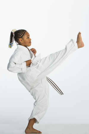 girl kick: Young mixed race girl posing in a karate kick position. She is wearing a karategi and is standing against a white background.