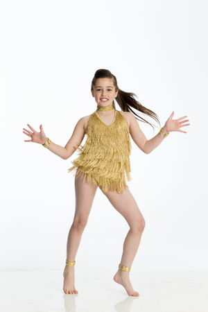 tassles: Young female dancer in gold costume.