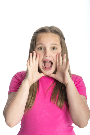 screaming: Young girl gesturing a shout at the camera. She is standing against a white background. Stock Photo