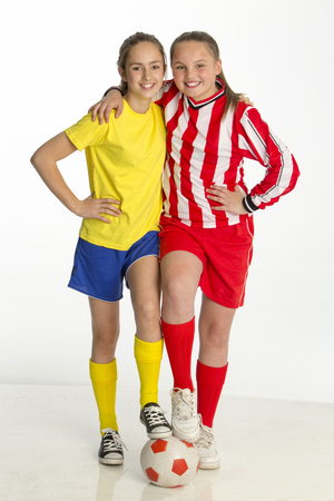 solids: Team captains of girls football match posing with a ball against a white background. They both have one foot on the ball and one arm round each other whilst smiling for the camera.