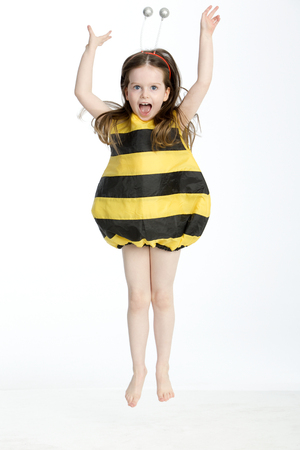midair: Little girl in a bumble bee costume posing in midair against a white background Stock Photo