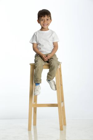 Cute young boy sitting on a stool against a white background, smiling for the camera.