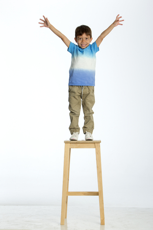 sensible: Little boy standing on a high stool with his arms out stretched. He is against a white background. Stock Photo