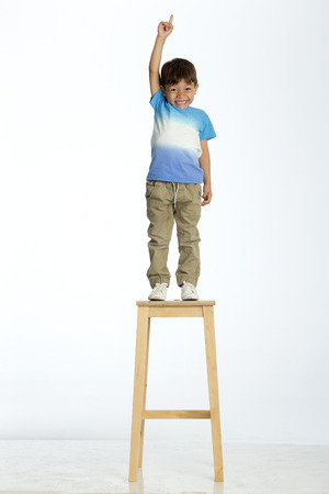 sensible: Little boy standing on a high stool, pointing up to the ceiling. He is against a white background.